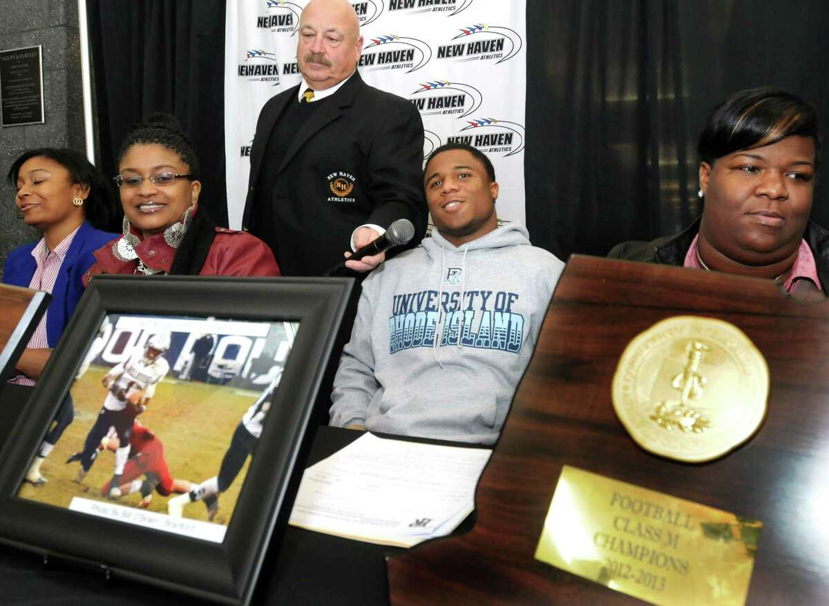 (Mara Lavitt - New Haven Register) ¬ February 6, 2014 New Haven ¬ It's high school signing day. From left: track athlete Tanaya Atkinson (going to Temple) and her mother Tammika, Supervisor of New Haven athletics Joe Canzanella, football playerHarold Cooper (going to URI) and his mother Marlo.