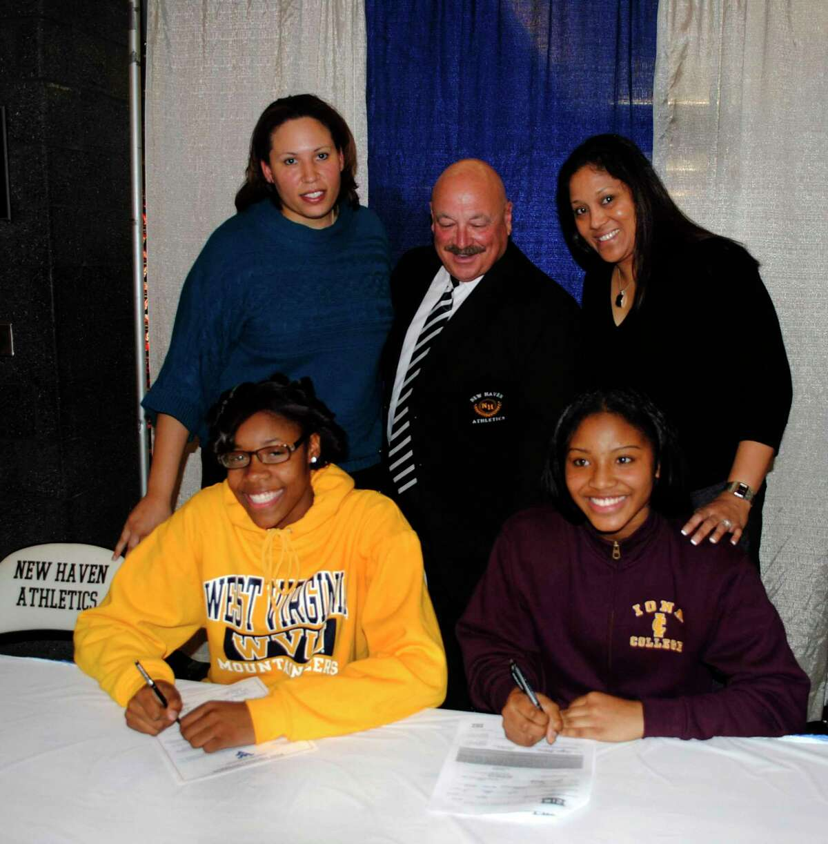 Hillhouse Girls Basketball Coach Catrina Hawley-Stewart, Supervisor of athletics and physical education Joseph Canzanella, and Wilbur Cross' Girls Basketball Coach Michelle Cabaldon watch as Bria Holmes (L) and Aaliyah Robinson sign their letters of intnet to play next year at West Virginia University and Iona College. 11/16/11 Kaitlin Bradshaw photo