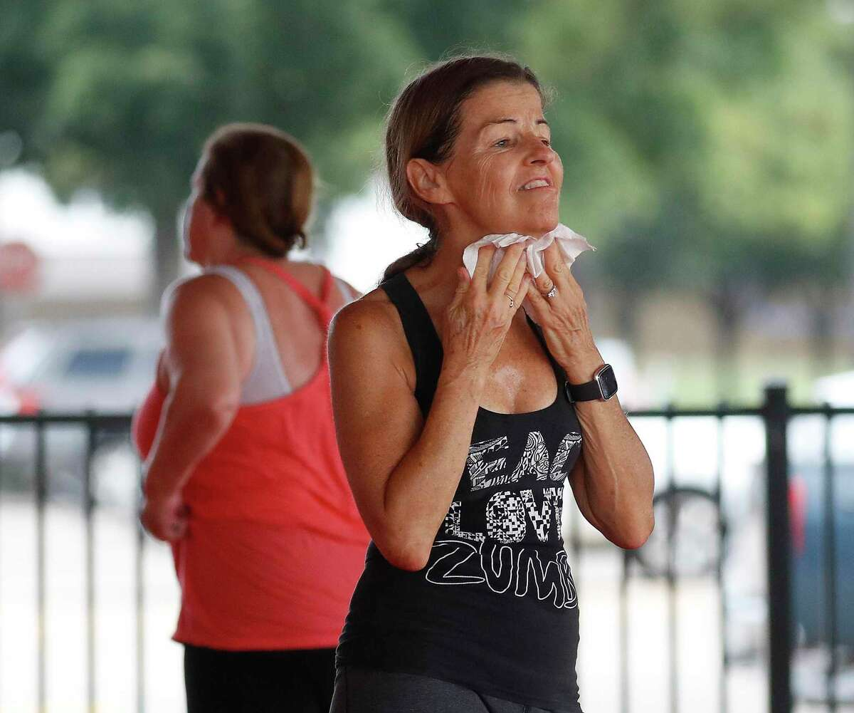 Laura McGrath wipes sweat off her face between dances as she attended Rafael Rios' outdoor Zumba class at Langham Creek Family YMCA, Saturday, July 11, 2020, in Houston.