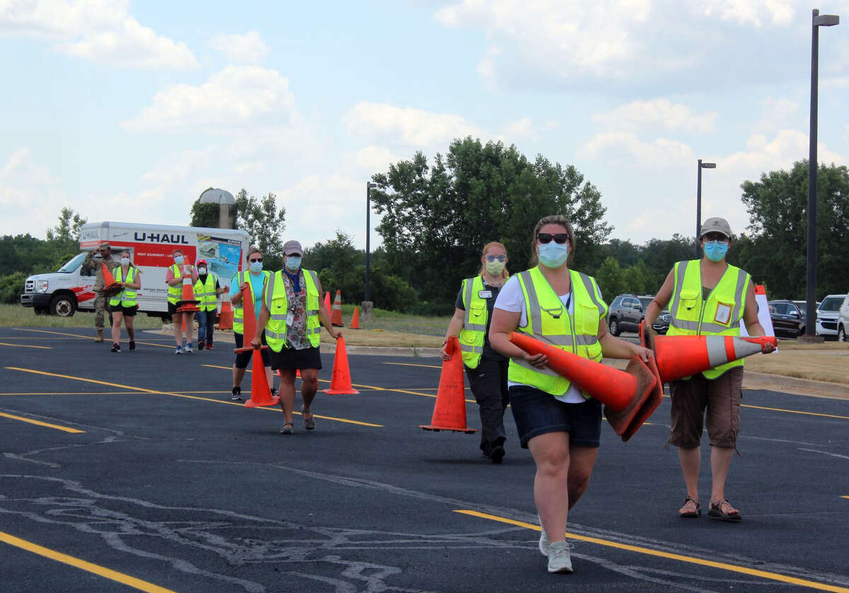 In this July 8, 2020, Pioneer file photo, a group of workers prepare to block of parts of Trinity Fellowship parking lot in Big Rapids to offer free COVID-19 testing to residents.