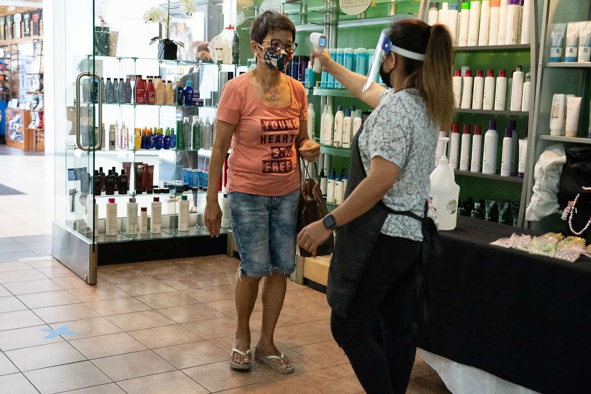 Imelda Galoay gets gets her temperature taken by Rizza Floreza at Lita's Hair Salon during their reopening after closing for four months during the coronavirus shutdown on Monday, July 13, 2020 in San Jose, Calif.