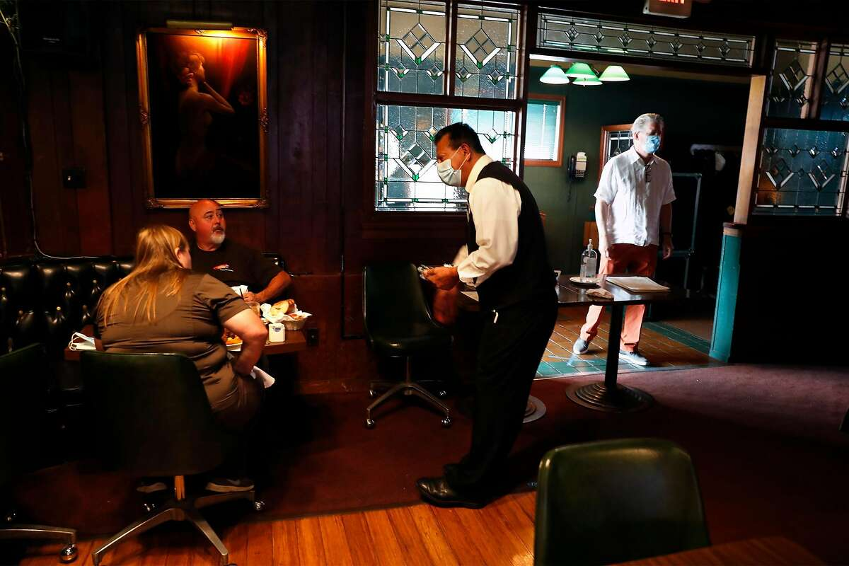 Val's Restaurant & Lounge's Oscar Anaya serves diners as co-owner Jeff Taylor (right) walks by in Daly City, Calif., on Monday, July 13, 2020. Earlier in the day, California Governor Gavin Newsom every county in California to close indoor restaurants, movie theaters and wineries.