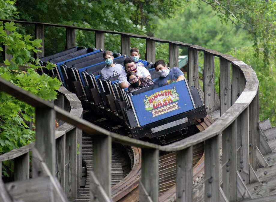 Riders wear their mask as they ride Boulder Dash at Lake Compounce July 7 in Bristol. Wearing masks in public and social distancing are necessary to keep the coronavirus from spreading widely. Photo: Aaron Flaum / Associated Press / Record-Journal
