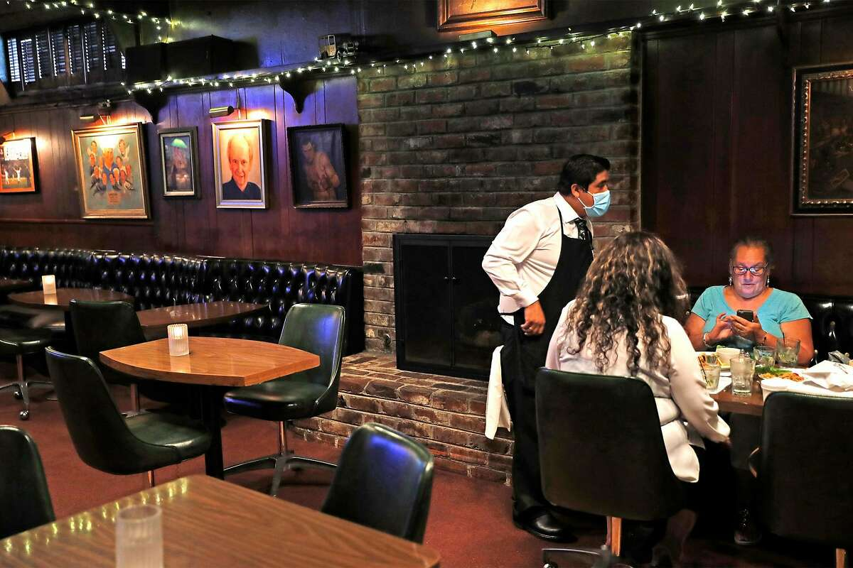 Val's Restaurant & Lounge's Oscar Anaya serves diners in Daly City, Calif., on Monday, July 13, 2020. Earlier in the day, California Governor Gavin Newsom every county in California to close indoor restaurants, movie theaters and wineries.