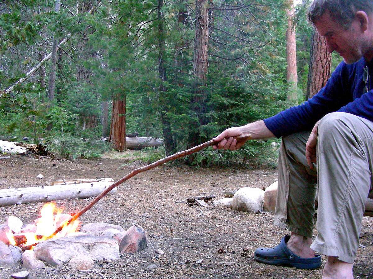 After a long day on the trail in the high Sierra wilderness, Michael Furniss tends a campfire along the headwaters of the Kern River in remote Sequoia National Park.
