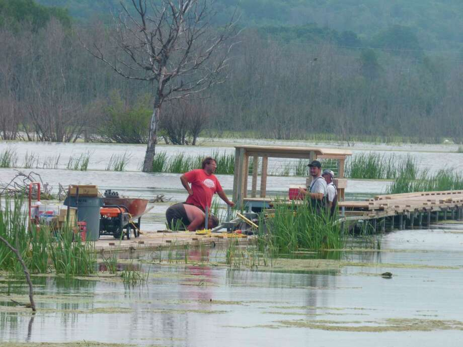 Workers raise a portion of boardwalk at the Arcadia Marsh Nature Preserve last week. Water levels at the marsh are tied to Portage Lake and Lake Michigan which have notched high water levels since 2019. (Scott Fraley/News Advocate)