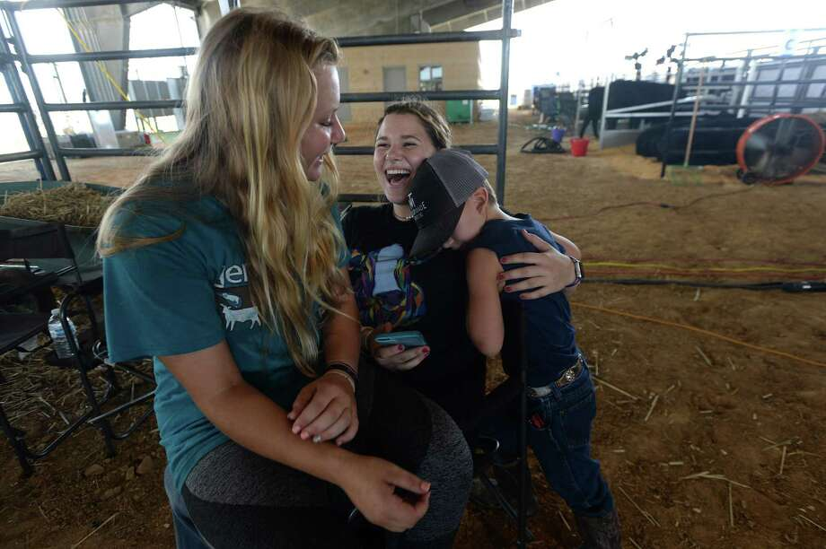 Railee Steele of Gainesville, FL, (left) and Maddie Carte of Live Oak, FL, joke with Truman Taylor, 8, of Lakeland, FL, in the barn as families arrive and prepare for the start of the National Junior Brangus Show that runs through the week at Ford Park. The 14-year-olds met doing shows and have been best friends for years. Photo taken Monday, July 13, 2020 Kim Brent/The Enterprise Photo: Kim Brent / The Enterprise / BEN