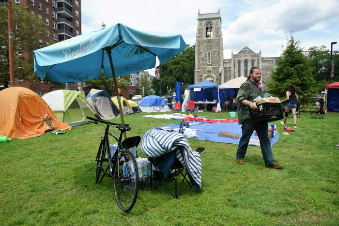 Bridgeport's Erik Kuranko carries supplies through the Latham Abolition Camp at Latham Park in Stamford, Conn. Monday, July 13, 2020. A group of protestors has been camped out at Latham Park since the weekend protesting the death of Steven Barrier, who died in police custody in October of 2019, and demanding reform from the local police department.