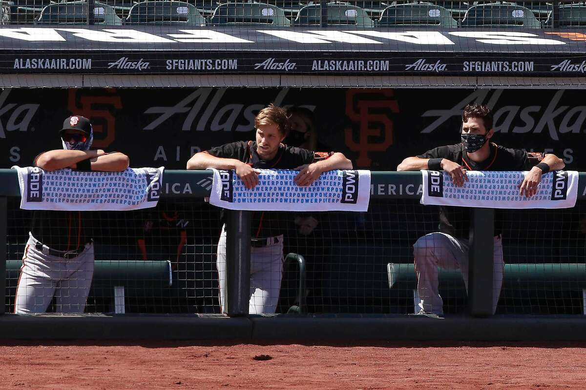 Members of the San Francisco Giants lean on towels as they watch practice from the dugout at Oracle Park in front of rows of empty seats on Monday, July 13, 2020 in San Francisco, Calif.