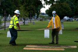 Workers prepare the test excavation site at Tulsa's Oaklawn Cemetery, where the city plans to dig for suspected mass graves from a 1921 race massacre.