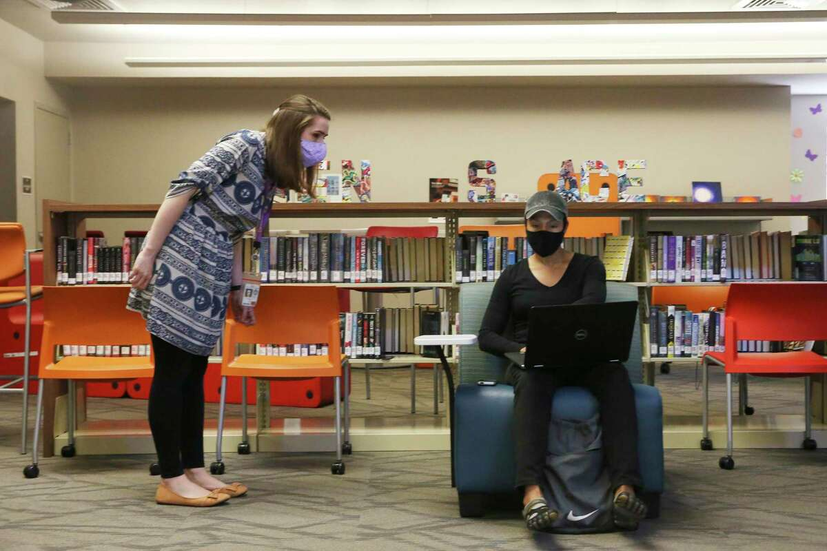 Librarian Daniella Toll, left, helps Briana Roberts find the correct WiFi signal at Collins Garden Library, one of several cooling centers open in San Antonio on Monday, July 13, 2020.