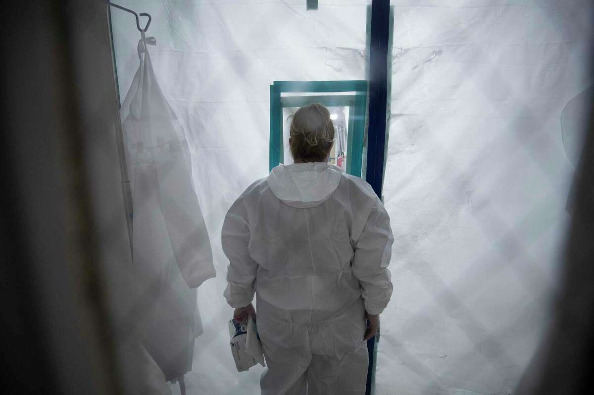 A nurse looks into one of the two COVID-19 intensive care wings at United Memorial Medical Center on Thursday, June 11, 2020, in Houston. The state of Texas has seen a spike in COVID-19 cases.