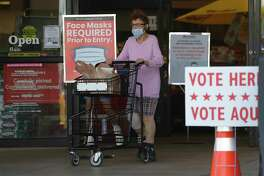 A shopper wearing a mask for protection against COVID-19 leaves a grocery store that is also searing as an early polling site, Thursday, July 9, 2020, in Austin, Texas.