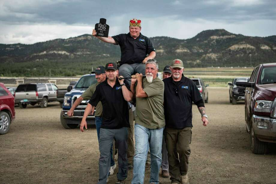 Midlander Paul Phillips, top, is hoisted on a chair by his team members after winning an international King of 2-Mile marksmanship competition. Phillips is also part of a 13-member team that holds a world record for hitting target with a rifle from four miles. (Photo provided)