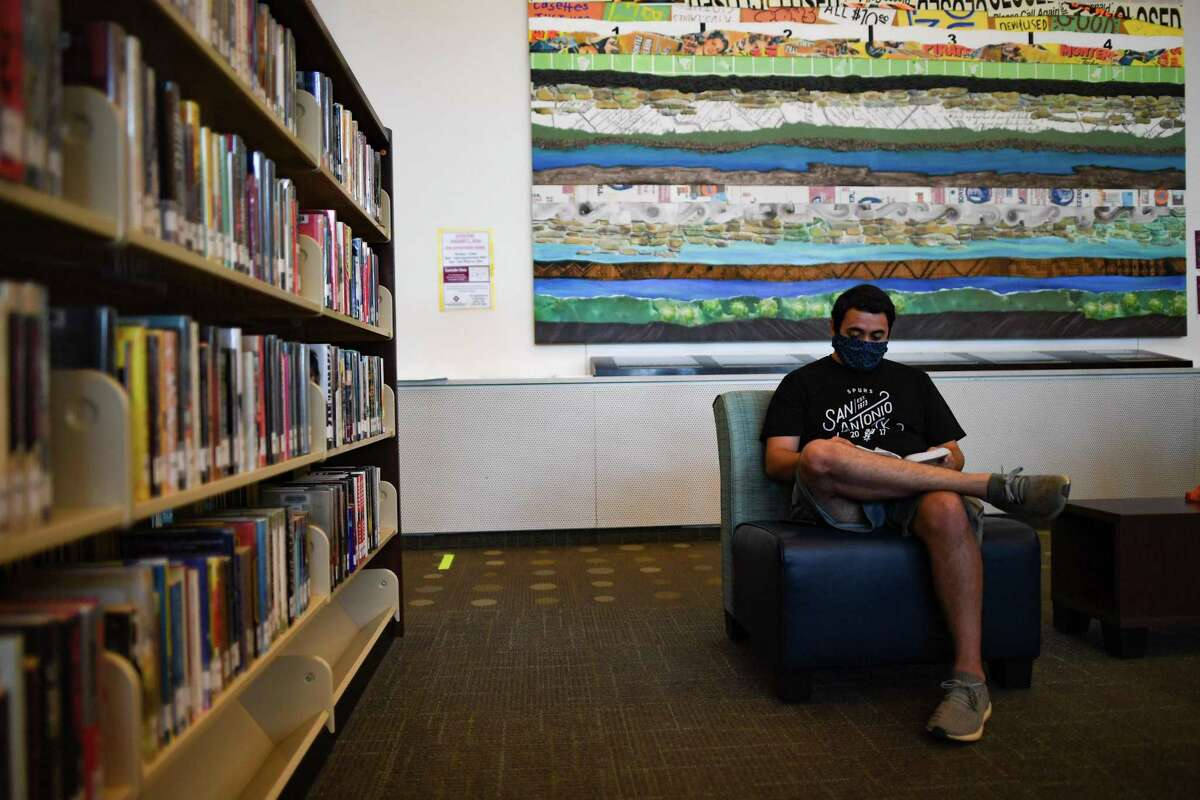 Cole Freddie reads a book while cooling off at Mission Branch Library, a designated City of San Antonio cooling zone, on Monday, July 13, 2020.