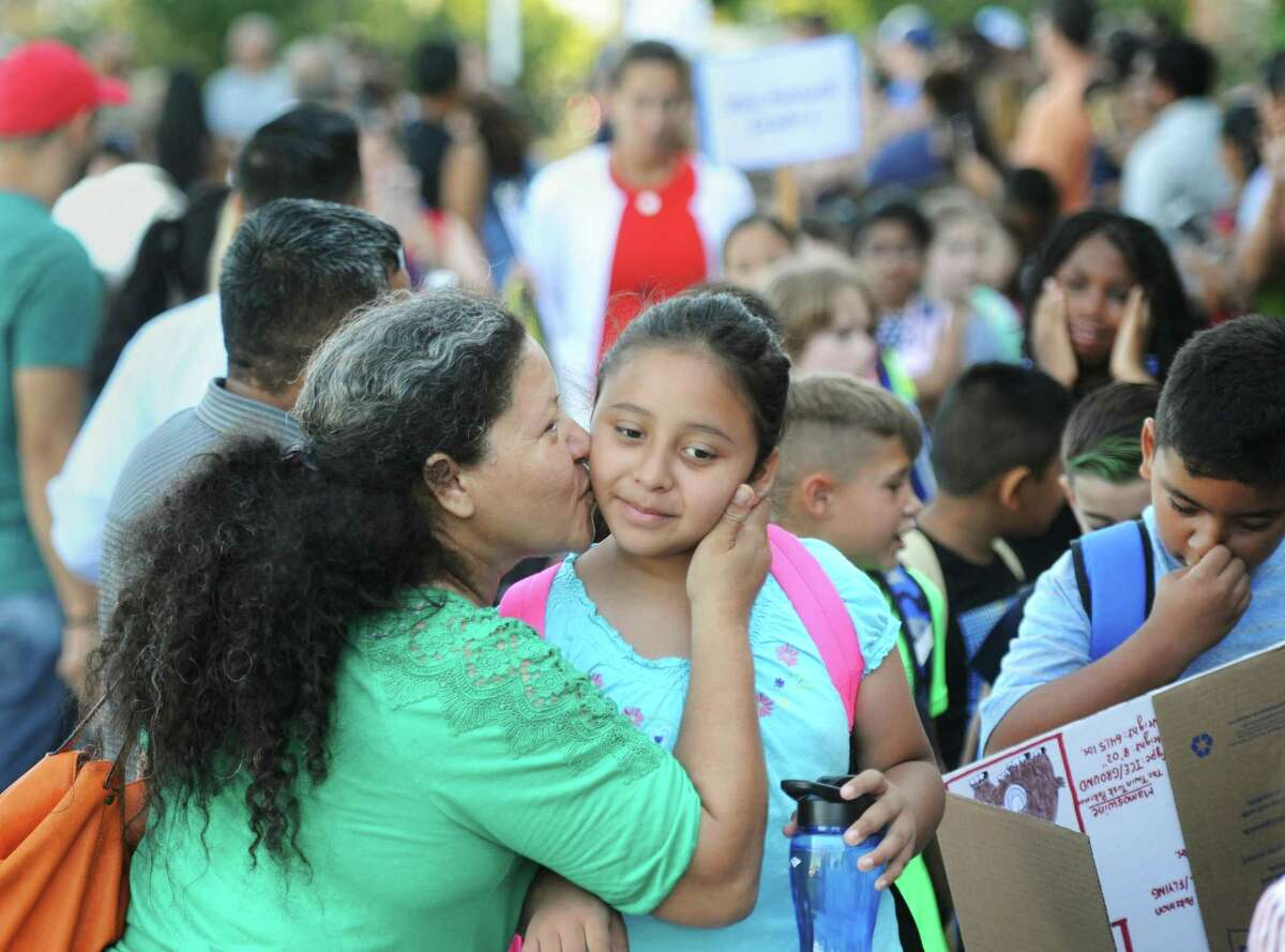 Lily Alvarez kisses her daughter, Rebecca, on her first day of third grade during the annual Parade of Students at Hamilton Avenue School in the Chickahominy section of Greenwich, Conn. Thursday, Aug. 30, 2018. What will the first day of school look like in 2020?