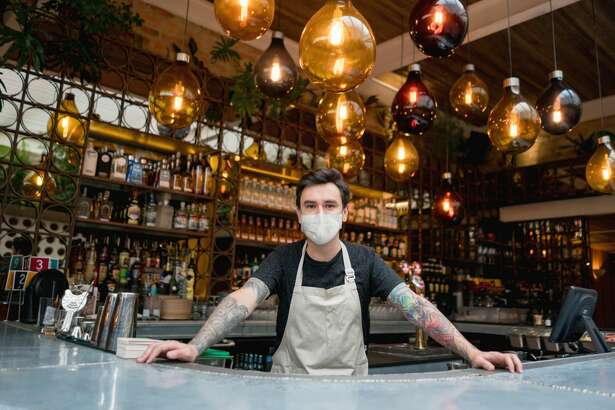 "Happy bartender working at a bar wearing a facemask to avoid the spread of coronavirus â€Â?"" COVID-19 lifestyle concepts"
