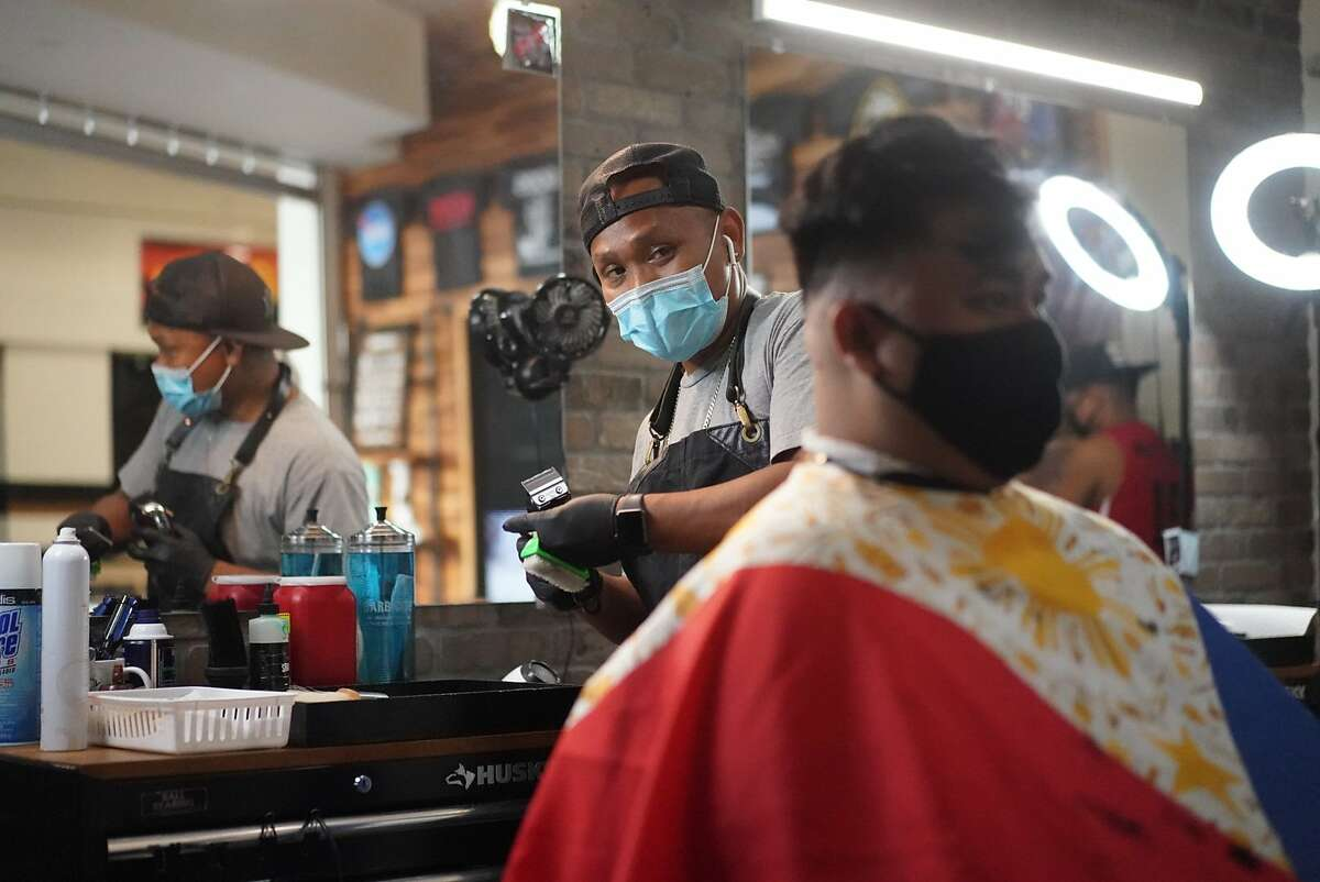 Streetset University Barbershop and Boutique, co-owner Case Dofredo give a haircut to Bart Bumanglag at their reopening after closing for four months during for the coronavirus shutdown on Monday, July 13, 2020 in San Jose, Calif.
