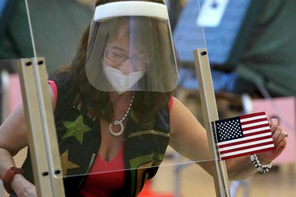 Beatriz Nelson, an election clerk, straightens a flag as she works behind a plastic barrier at her desk wearing a face mask and face shield as people vote at the Metropolitan Multi-Service Center, 1475 West Gray, Friday, July 10, 2020, in Houston.