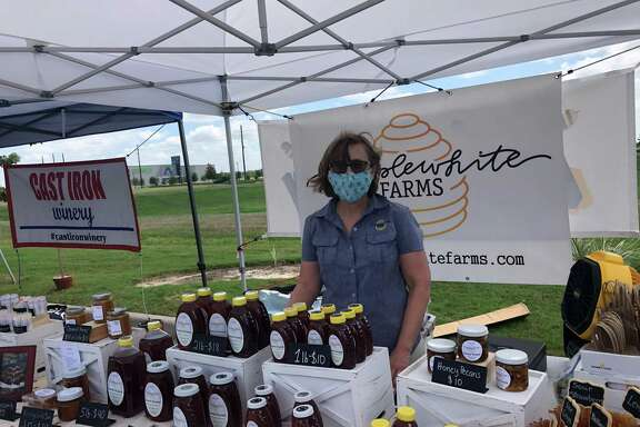 Tracey Grimme sells honey from Hepplewhite Farms at a monthly farmers market outside Whiskey Cake in Katy on Saturday, July 11.