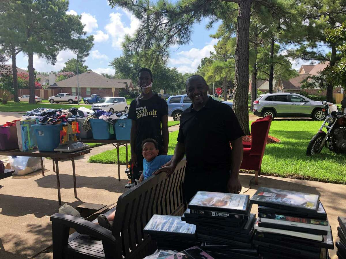 Lawrence, from left, Greyson and Larry Williams pose at a garage sale they were holding in Katy on Saturday, July 11.