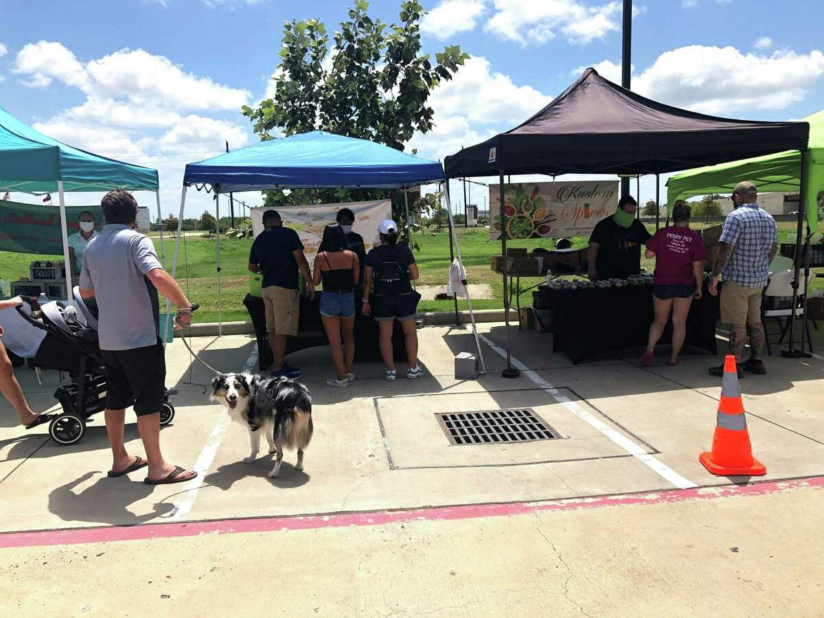 Customers shop at a monthly farmers market outside Whiskey Cake in Katy on Saturday, July 11.