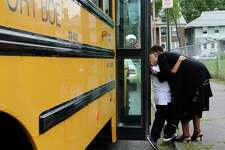 Hall School principal Veronica Thomas and fourth-grader Joshua Martinez greet each other as he steps off the school bus on the first day of school in Bridgeport, CT on Wednesday August 25, 2010.