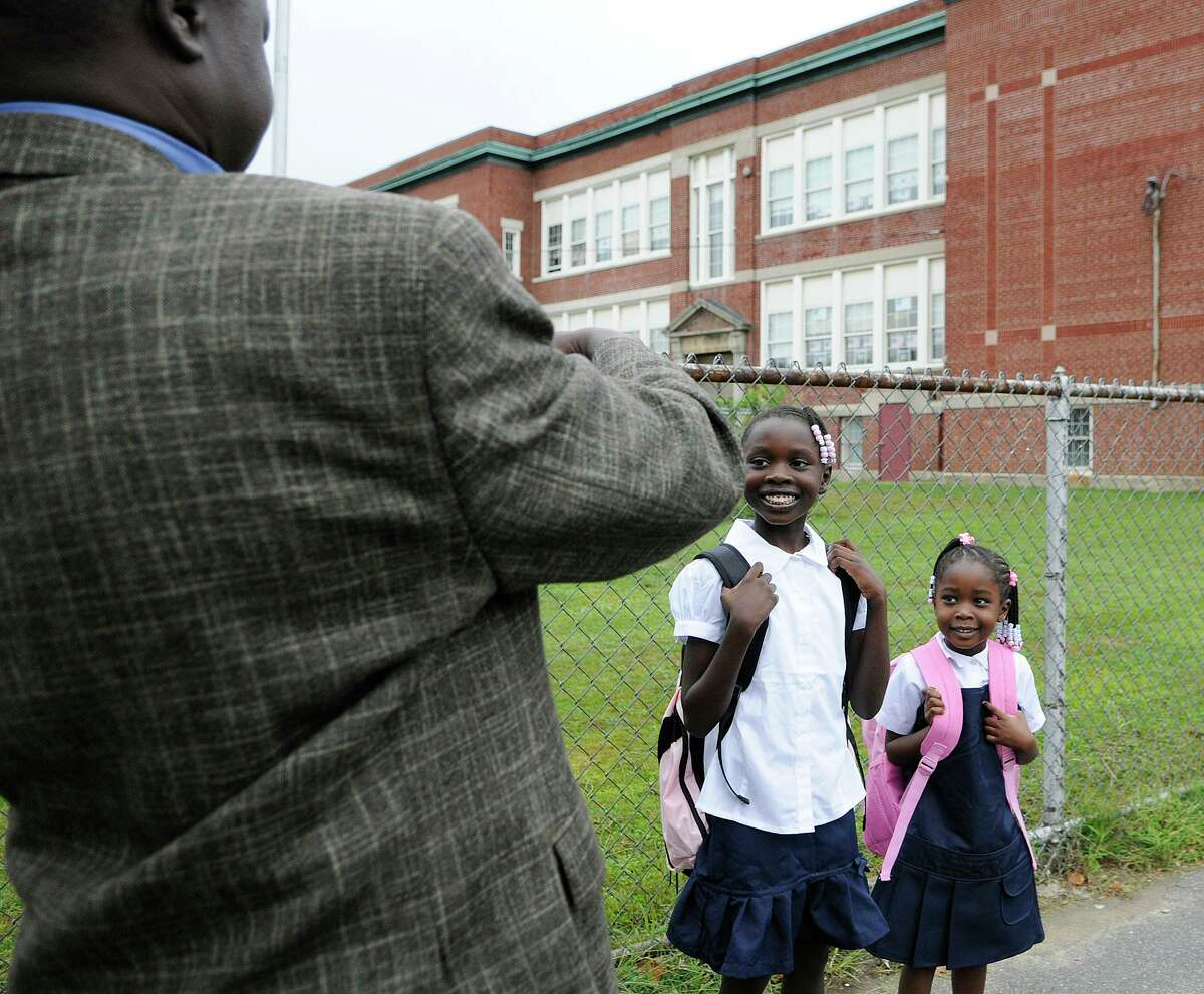 Bismark Elfayous snaps a photo of daughters Dayii, 9, and Angowa, 4, as they wait for the bus to take them to the first day of the school year at High Horizons Magnet School in Bridgeport, CT on Wednesday August 25, 2010.