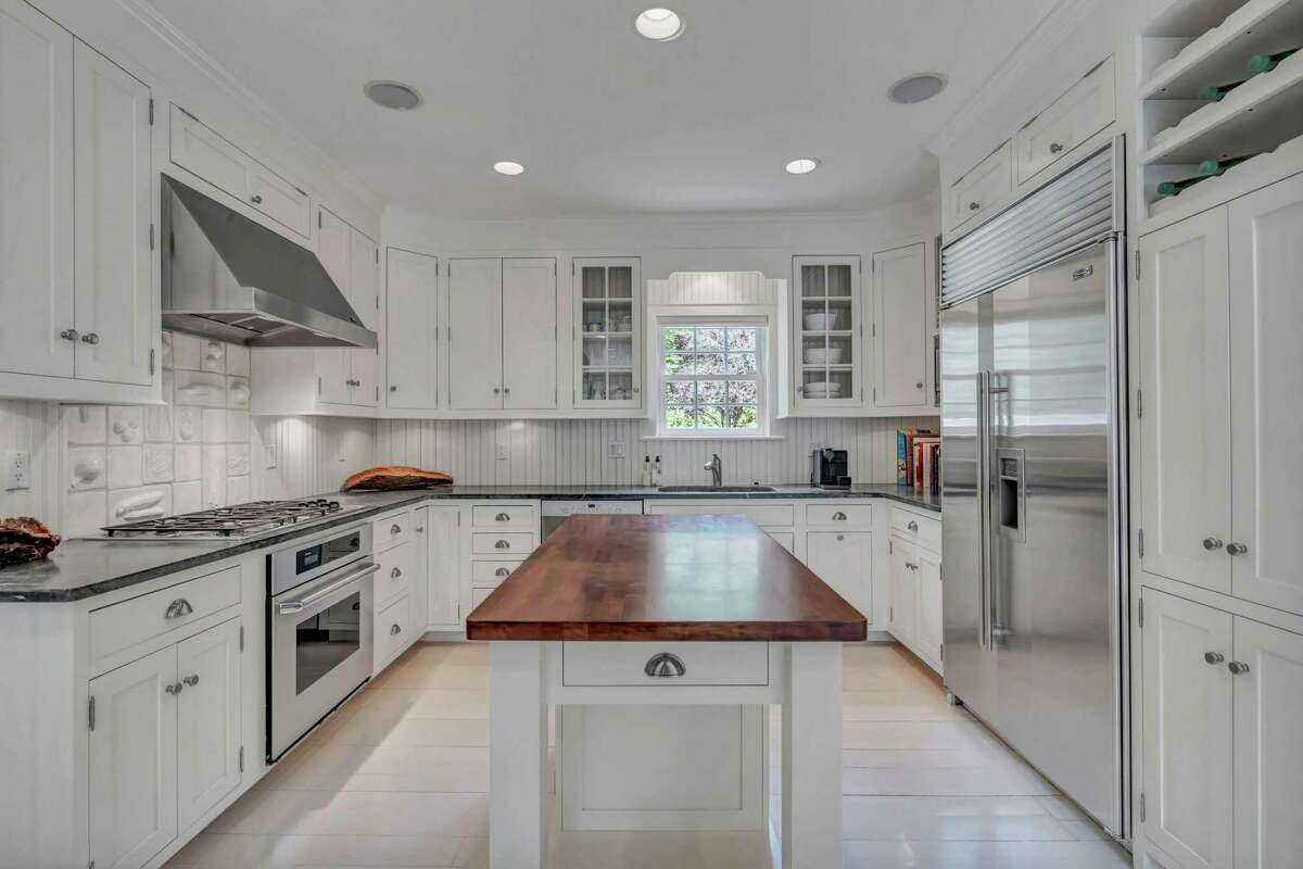 The renovated chef's kitchen features extensive custom cabinetry, a built-in wine rack, granite counters, upscale finishes and a light-filled casual dining area.