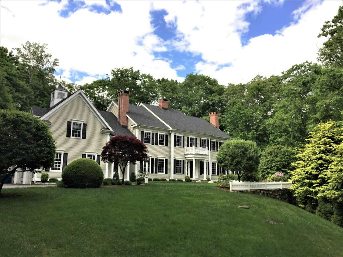 """The colonial house at 5 Overbrook Lane in Lower Weston is classic and """"casual yet elegant,"""" with 15 rooms and 6,412 square feet of living and entertaining space. Many recent upgrades were made to this house including the installation of a new wood shingle roof, a well, landscaping and air conditioning. The house also enjoys custom millwork and 9-foot ceilings. In the formal living room there is a fireplace with a decorative mantel. In the formal dining room there is another marble fireplace and wainscoting on the lower walls."""