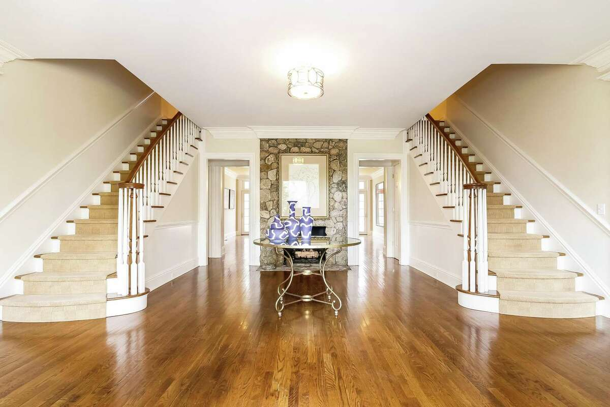 The center hall colonial the reception hall features a dramatic split staircase, with flights to the second floor flanking the foyer's floor-to-ceiling stone fireplace. The front door opens into a grand foyer with wainscoting and dentil crown molding.