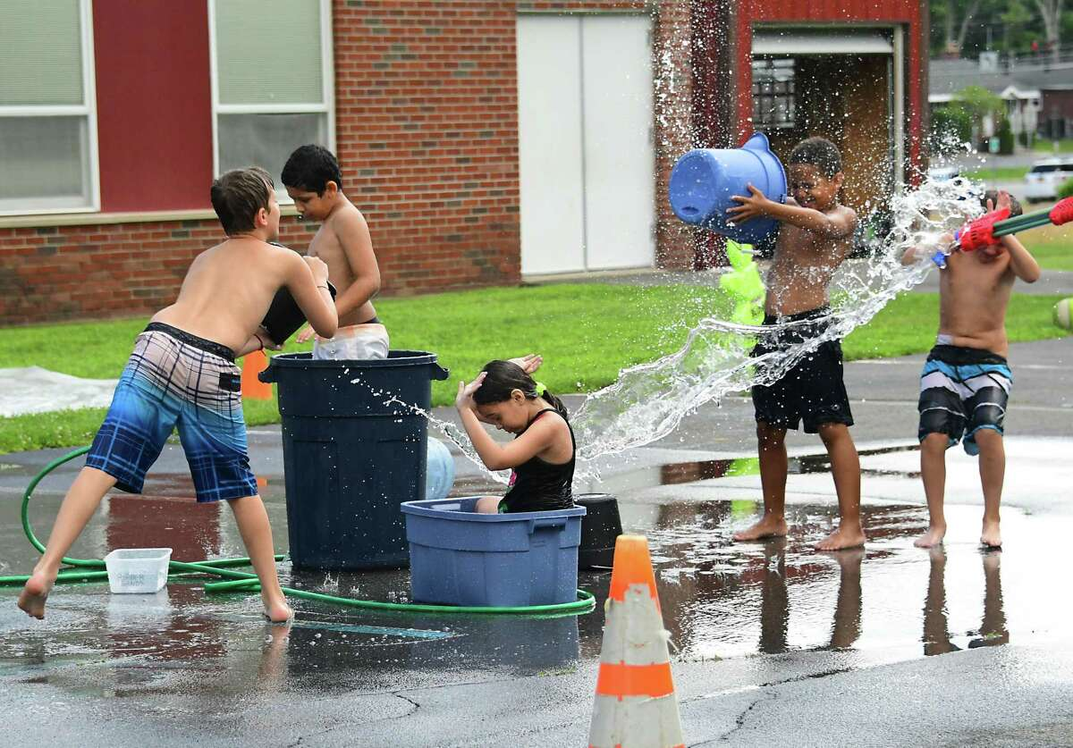 From left, Branden Redick, 11, Arkaiss Rosario-Blanco, 10, Kylie McGough, 10, Roman Harris, 8, and Carter Sale, 9, enjoy water play time at TSL (Together, Sharing, Learning) Kids Crew summer camp at the former Christ Lutheran Church on Western Ave. Tuesday, July 14, 2020 in Guilderland, N.Y. (Lori Van Buren/Times Union)