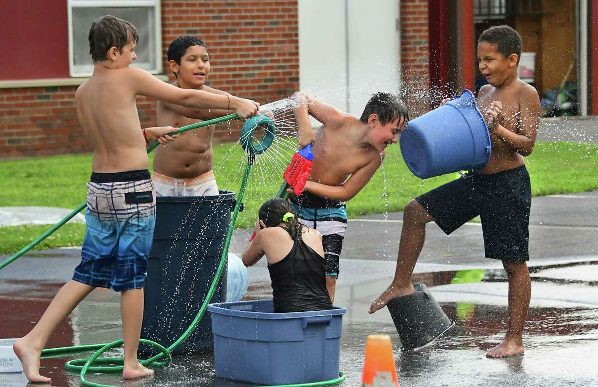 From left, Branden Redick, 11, Arkaiss Rosario-Blanco, 10, Kylie McGough, 10, Carter Sale, 9, and Roman Harris, 8, enjoy water play time at TSL (Together, Sharing, Learning) Kids Crew summer camp at the former Christ Lutheran Church on Western Ave. Tuesday, July 14, 2020 in Guilderland, N.Y. (Lori Van Buren/Times Union)