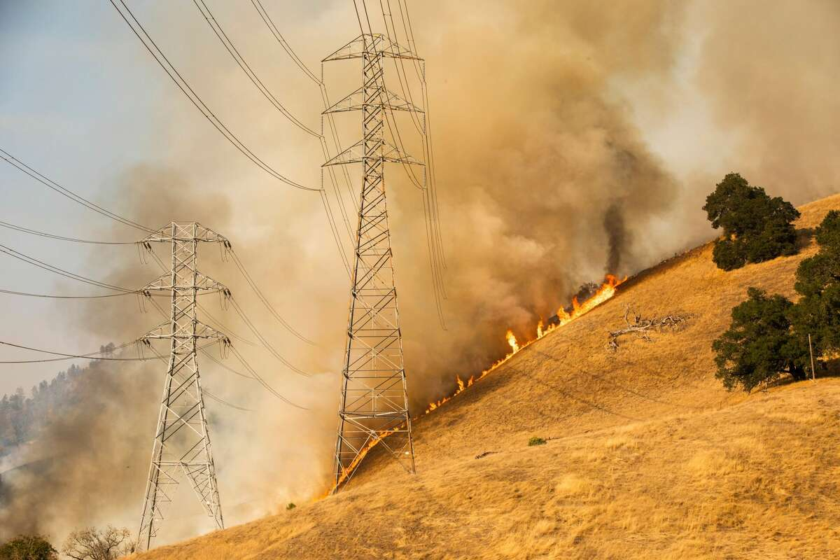 A back fire set by fire fighters burns a hillside behind PG&E power lines during firefighting operations to battle the Kincade Fire in Healdsburg, California on October 26, 2019. - US officials on October 26 ordered about 50,000 people to evacuate parts of the San Francisco Bay area in California as hot dry winds are forecast to fan raging wildfires.