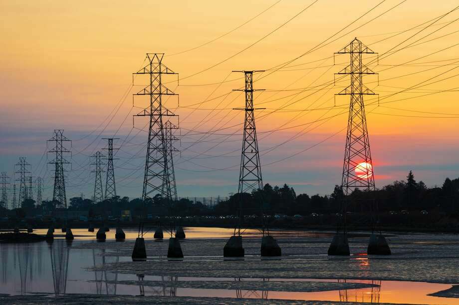 Power transmission tower is silhouetted by the rising sun in Burlingame, California on October 26, 2019. Potentially historic windstorm coming to the San Francisco Bay Area may prompt Pacific Gas and Electric Company, PG&E to shutoff power to as many as 2 million people to lower devastating wildfire risk. Photo: NurPhoto/NurPhoto Via Getty Images / Yichuan Cao/NurPhoto