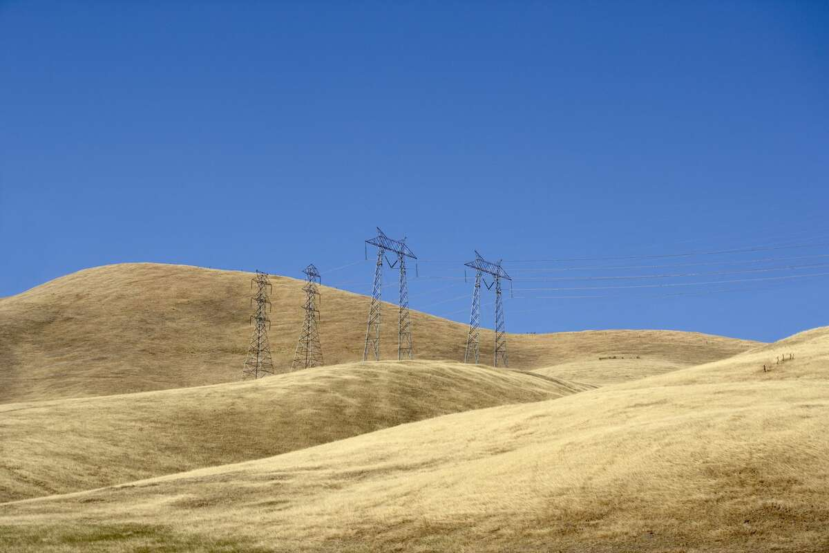 Dry grass covers hills in California on a windy day.