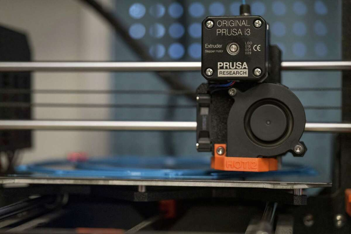 A 3D printer makes head straps for protective face shields.