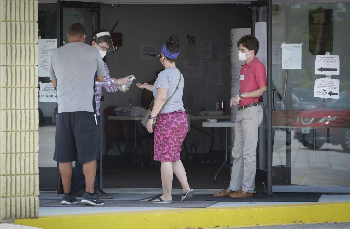 Voters are greeted by volunteers who open doors and offer hand sanitizer at the St. Mary's Center, 3006 Rosedale St., Tuesday, July 14, 2020, in Houston.