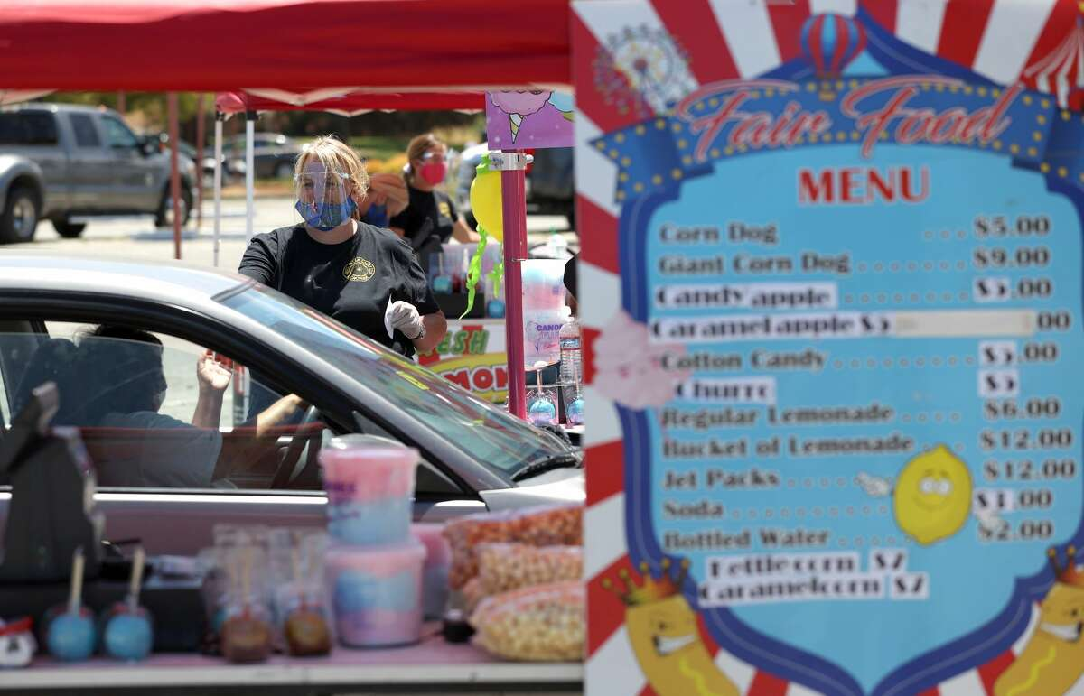 Stacee Hoffee helps a customer during a drive-thru food fair in the parking lot at the Veterans Memorial Auditorium on July 10, 2020 in San Rafael, California.