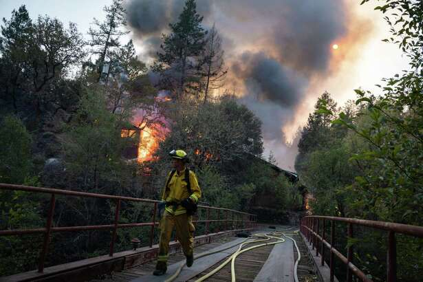 A firefighter works to extinguish a burning building off Highway 128 in Sonoma County, Calif., on Oct. 29, 2019.