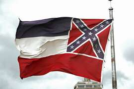 File-This June 25, 2020, file photo shows a Mississippi state flag flying outside the Capitol in Jackson, Miss. Mississippi will surrender the Confederate battle emblem from its state flag, more than a century after white supremacist legislators embedded it there a generation after the South lost the Civil War. Mississippi's House and Senate voted in succession Sunday, June 28, 2020, to retire the flag, with broad bipartisan support. Republican Gov. Tate Reeves has said he will sign the bill, and the state flag would lose its official status as soon as he signs the measure.  (AP Photo/Rogelio V. Solis, File)