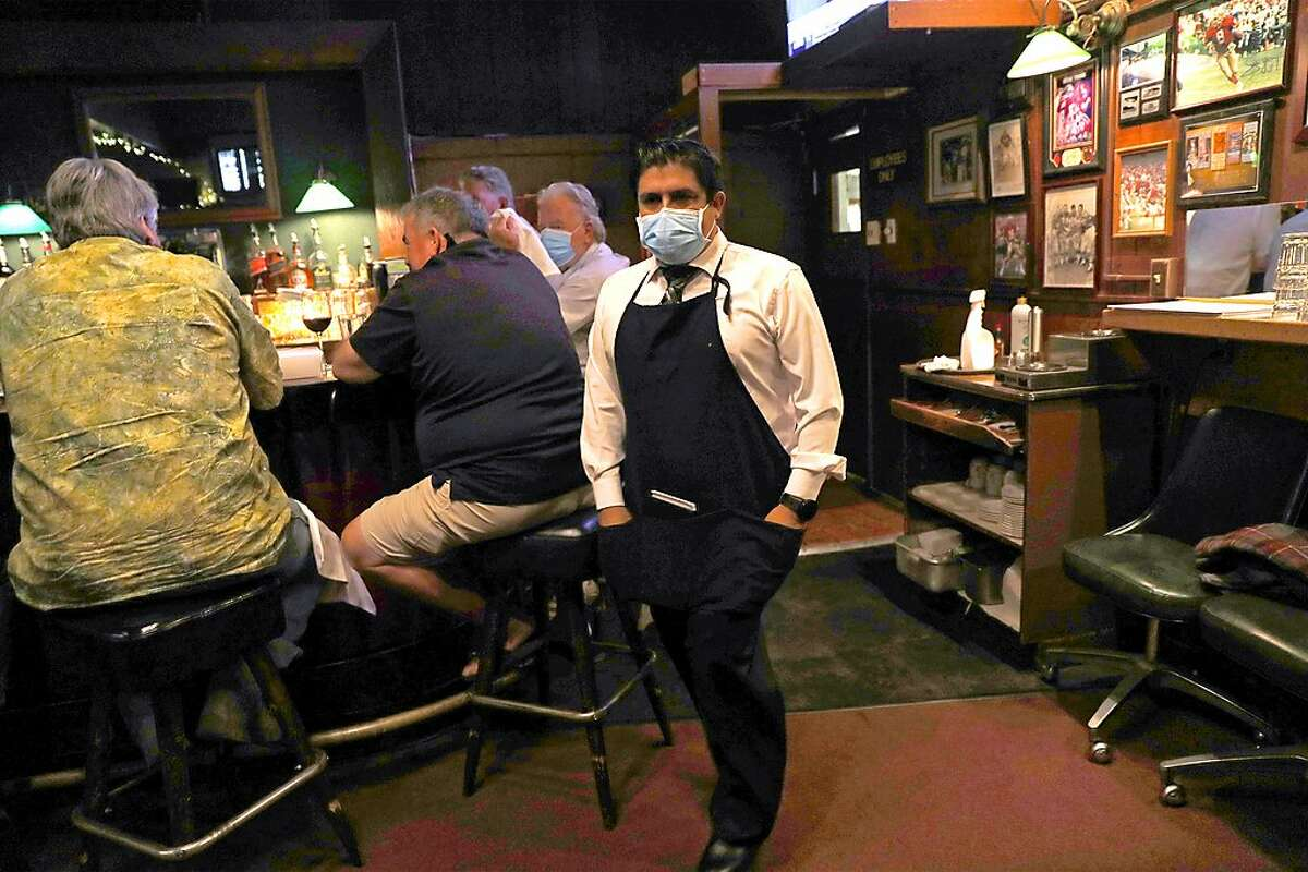 Val's Restaurant & Lounge server Oscar Anaya walks past a group of men seated at the bar in Daly City, Calif., on Monday, July 13, 2020. Earlier in the day, California Governor Gavin Newsom every county in California to close indoor restaurants, movie theaters and wineries.