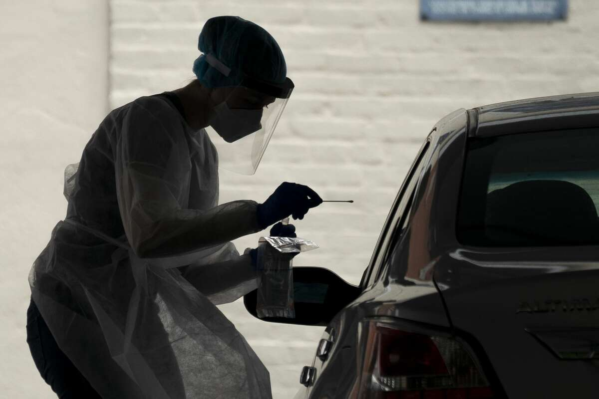 WASHINGTON, DC - MAY 26: A medical professional administers a coronavirus test at a drive-thru testing site run by George Washington University Hospital, May 26, 2020 in Washington, DC. Dr. Deborah Birx, the lead coordinator of the White House coronavirus task force, said on Friday that the District of Columbia and its suburbs have the highest rate in the country of people testing positive for the infection. (Photo by Drew Angerer/Getty Images)
