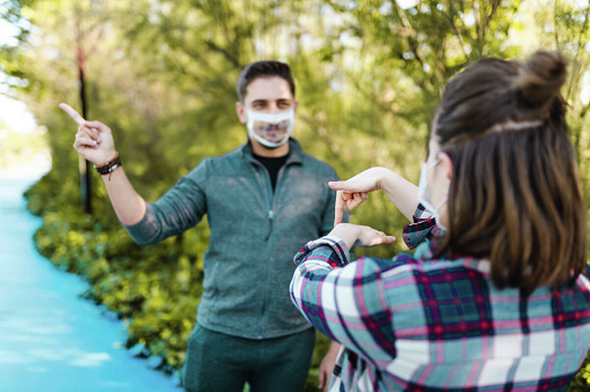 Deaf and hard hearing young adults wear special face coverings that allow for lip-reading.
