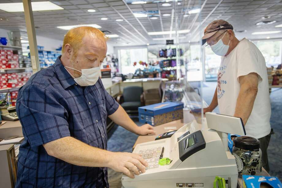 Andy McGee, left, rings up an order for customer Jerry Schuitman Tuesday, July 14, 2020 at Circle Quality Shoes. Governor Whitmer's new executive order doesn't change much for the store's day-to-day operations, they were already requiring face coverings inside. (Katy Kildee/kkildee@mdn.net) Photo: (Katy Kildee/kkildee@mdn.net)