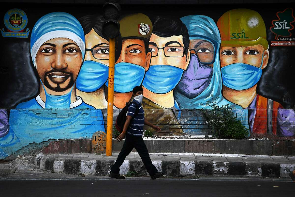 A man walks past a mural of frontline workers.