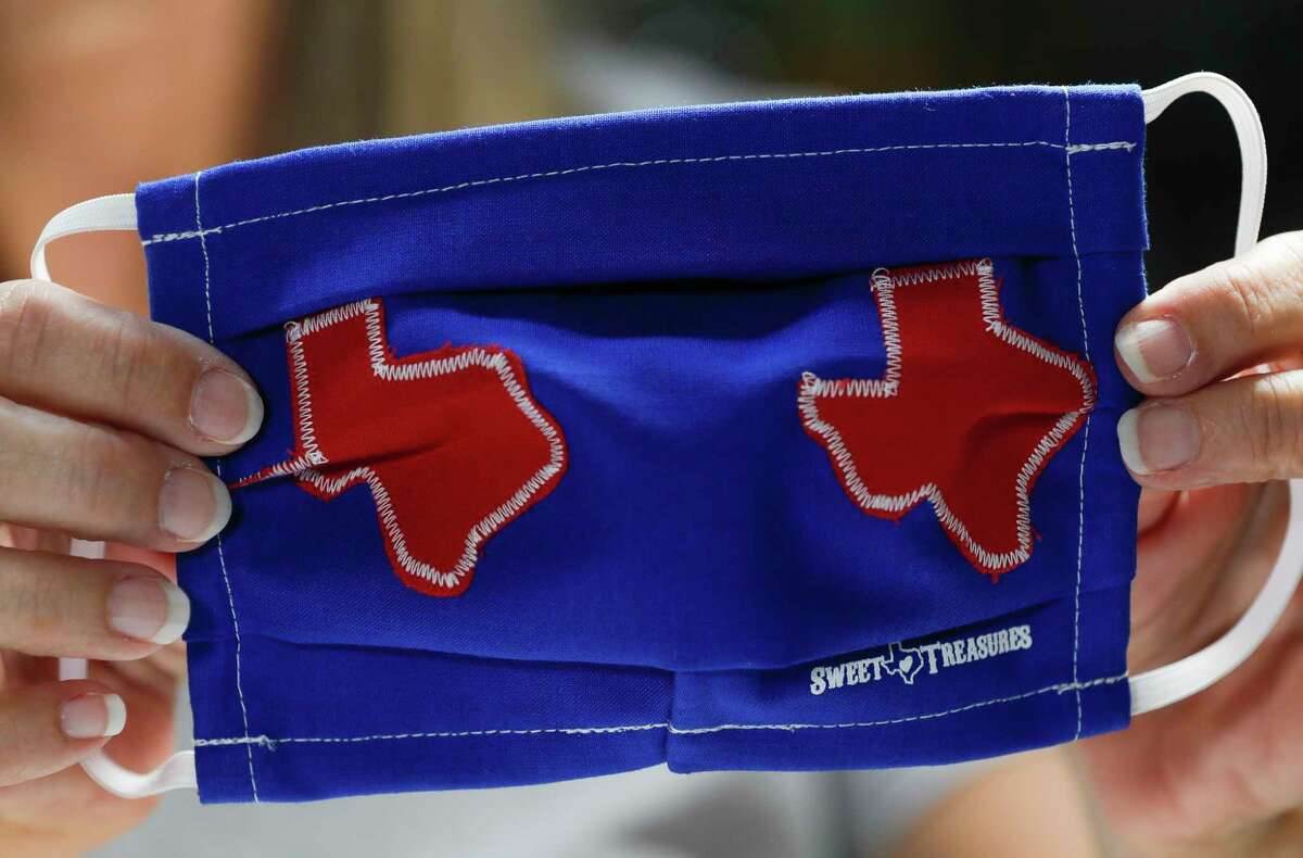 Toni Rodriguez checks the stitching on the back of a custom Texas-themed mask at Sweet Texas Treasures Boutique, Friday, July 3, 2020, in Montgomery. Gov. Greg Abbott's statewide face-covering order, which targets Texan counties with more than 20 coronavirus cases, went into effect at noon in an effort to slow the spread of COVID-19.