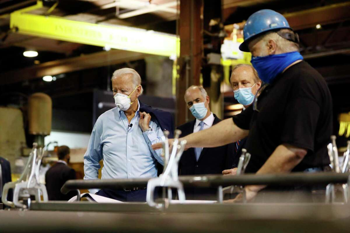 Democratic presidential candidate, former Vice President Joe Biden, from left, Sen. Bob Casey, D-Pa., and McGregor Industries owner Bob McGregor listen to First Class Fitter Michael Phillips during a tour of the metal fabricating facility in Dunmore, Pa. Biden is pledging to define his presidency by a sweeping economic agenda beyond anything Americans have seen since the Great Depression and the industrial mobilization for World War II.