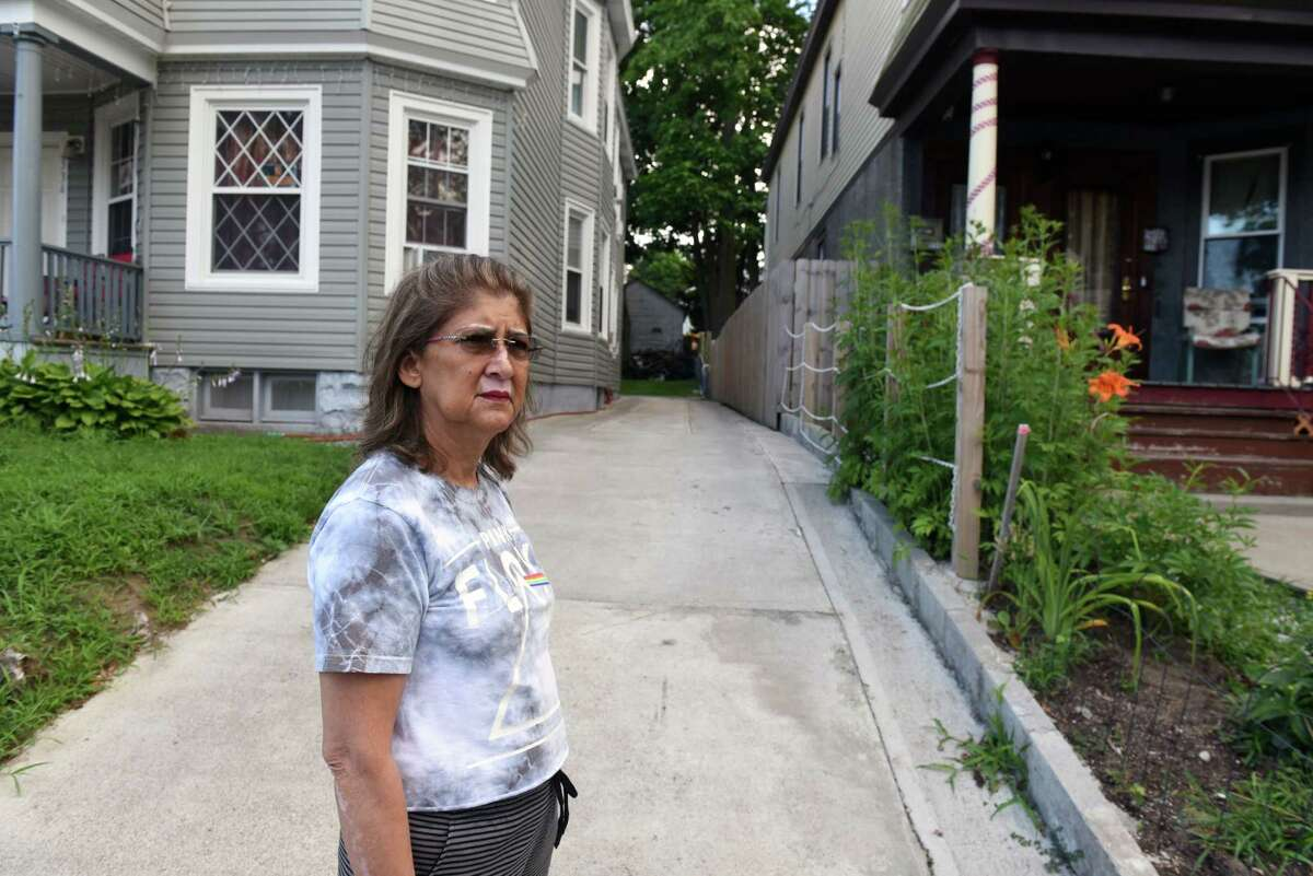 Carol Eto stands near a fence separating her property from her neighbor, Yugeshwar Gaindarpersaud, which she says has caused friction between the two on Tuesday, July 14, 2020, in Schenectady, N.Y. Gaindarpersaud was recently involved in an altercation with a city cop, hastening local police reforms. (Will Waldron/Times Union)