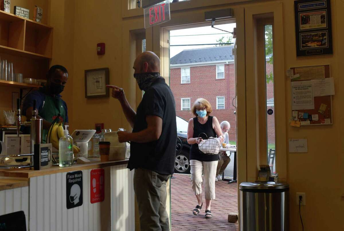 Jean Fenton, left, helps a customer at Abyssinia Market and Coffee House in Alexandria, Va., on Saturday, July 11, 2020.